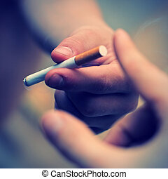 Pass a Cigarette - Toned photo of Hand take a Cigarette from...