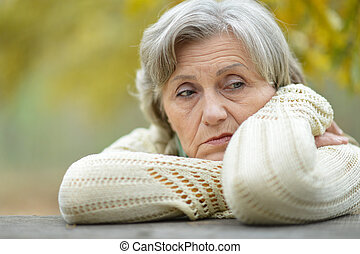 Sad old woman in park - Nice sad old woman on the autumn...