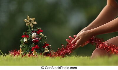 girl decorates the Christmas tree with red rain