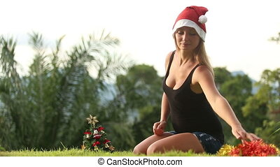 young girl in christmas hat dress gold rain on her neck near...