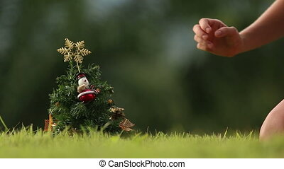 girl takes a star from Christmas tree with green jungle on...