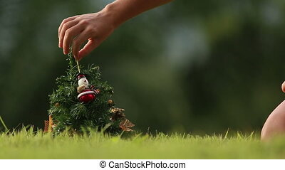 girl takes snowman from Christmas tree with green jungle on...