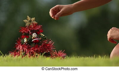 girl removes garland from Christmas tree with green jungle...