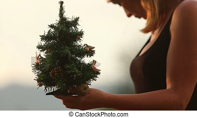 girl corrects christmas tree - girl corrects small green...