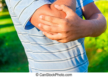 man holding his hand sore elbow