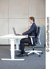 correct sitting position at workstation business man in suit...