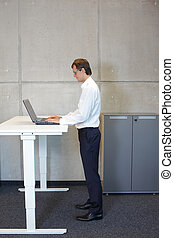 business man standing at desk - business man with eyeglasses...