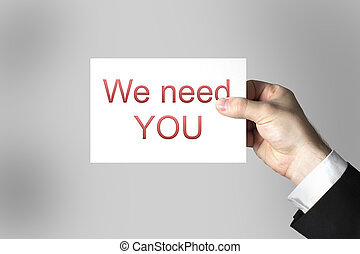 hand holding sign we need you - businessman hand holding...