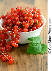 bowl with red currant on table