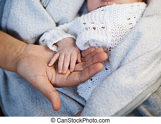 Mom keeps miniature hand newborn baby in hands - Mom keeps a...