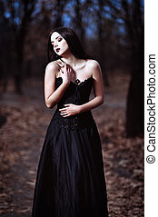 A beautiful sad goth girl stands in grove - A beautiful sad...