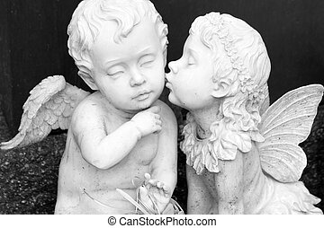 kissing couple of angelic figurines isolated on dark...