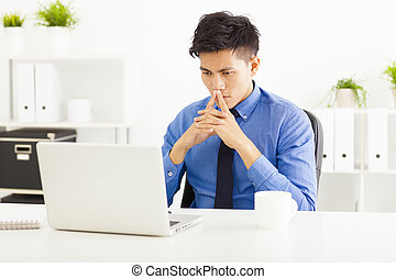 Young asian business man watching laptop and thinking