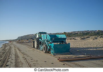 Cleaning the beach - A tractor with a trailer cleaning a...