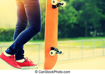 woman skateboarder legs at skatepark