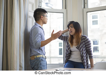 Asian couple arguing in their living room.
