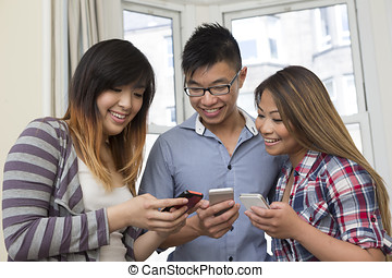 Happy Asia using their mobile phones. - Group of young Asian...