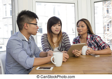 Asian friends looking at a digital Tablet. - Group of young...