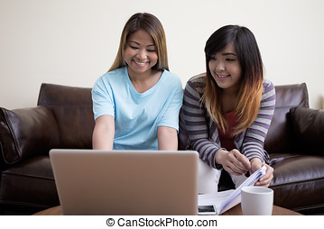 Two Asian female friends sitting at home, using a laptop pc...