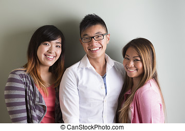 Group portrait of 3 happy Asian people. Looking at camera,...