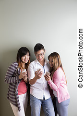 Happy Asian students using their cell phones - Group of...