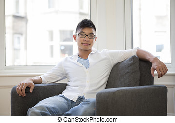 Portrait of a trendy Asian man at home. Chinese man relaxing...