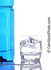 Bottle and glass of mineral water with droplets reflected on...