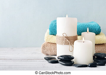 Candles with towels on light blue background