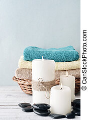 Candles with towels in basket on light blue background