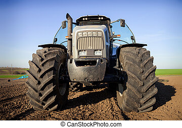 Agricultural tractor standing on the plowed ground