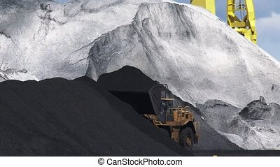 Transshipment of coal in Dutch port. Shovel at coal heap -...