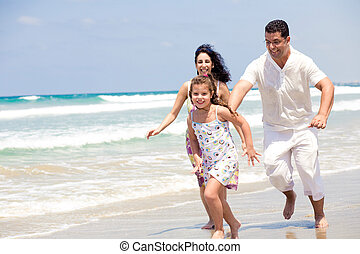Family running on the beach - Family having fun as they run...