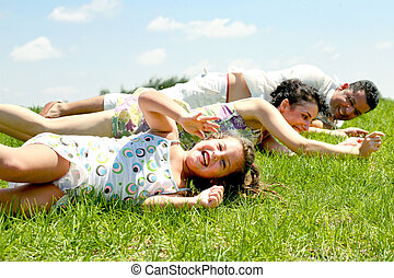 Family lifestyle portrait - Family lying on lush green...