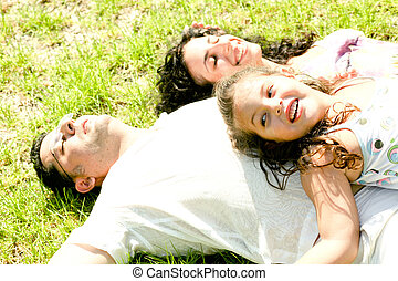 Family at rest - Couple lie down on ground while kid plays...