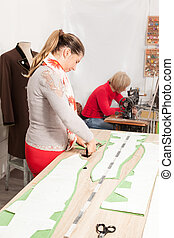 Taylor shop - two happy seamstresses working in a taylor...