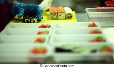 Cook lays out sushi into containers - View of cook lays out...