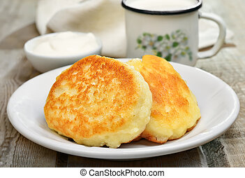 Fritters on rustic table - Fritters on white plate, sour...