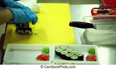 Chef cooks sushi and rolls on cutting board