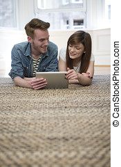 Couple relaxing together at home with tablet computer. Happy...