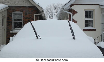 Winter wipers. - Snow covered car with wipers up. Drivers in...