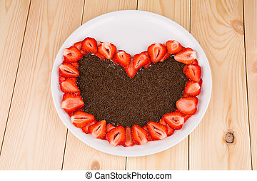 Strawberry cake with chocolate in heart shape, top view