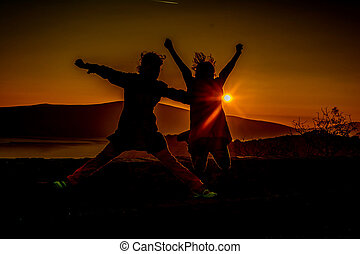 Two little girls jumping in the sunset - Two little girls...