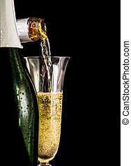 Champagne is poured into glass on a dark background