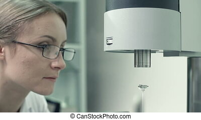Laboratory Balance - Female scientist using laboratory...