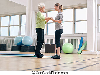 Trainer helping senior woman exercising with a bosu balance...
