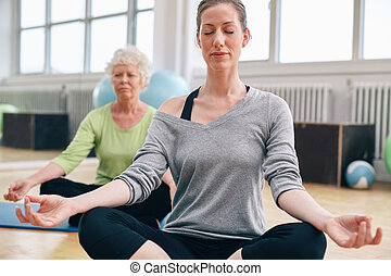 Women relaxing and meditating in their yoga class at gym....