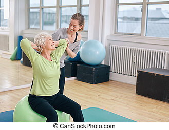 Happy senior woman exercising with female instructor -...