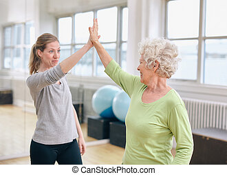 Senior woman rejoicing health success with her trainer at rehab