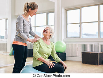 Older woman assisted by personal trainer at gym - Female...