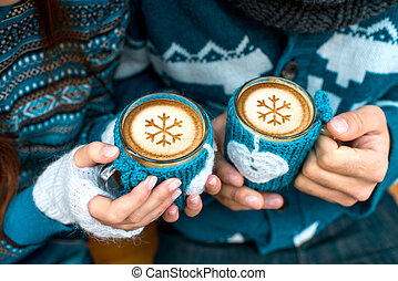 Couple with coffee cups in winter - Couple holding knitted...